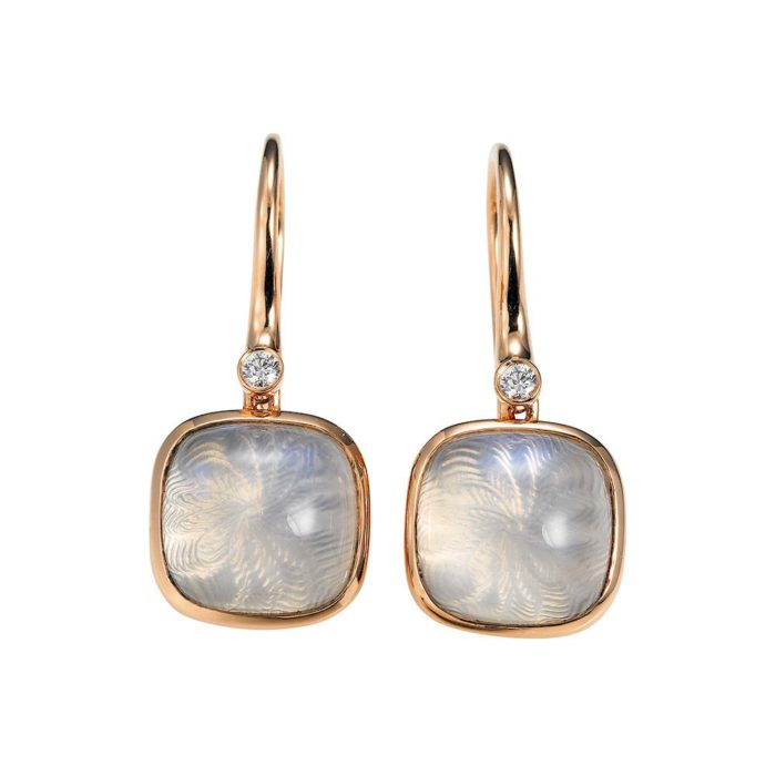 Gold earrings with blue shimmering gemstone on guilloched surface with diamonds