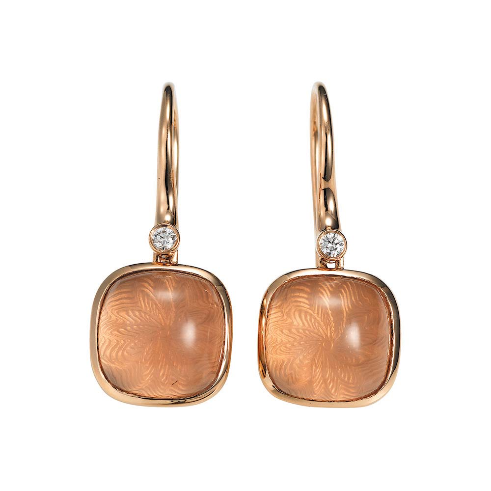 Gold earrings with peach coloured gemstone on guiloched surface with diamonds
