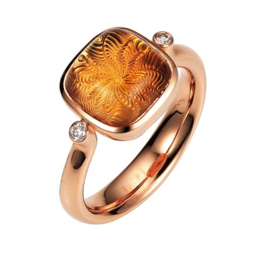 Gold ring with yellow gemstone on guilloched surface with diamonds
