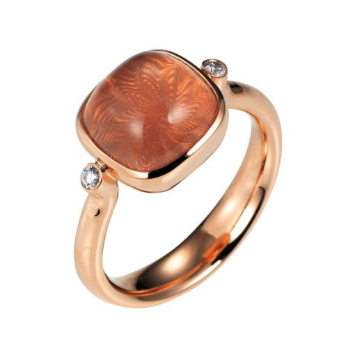 Gold ring with peach coloured gemstone on guilloched surface with diamonds