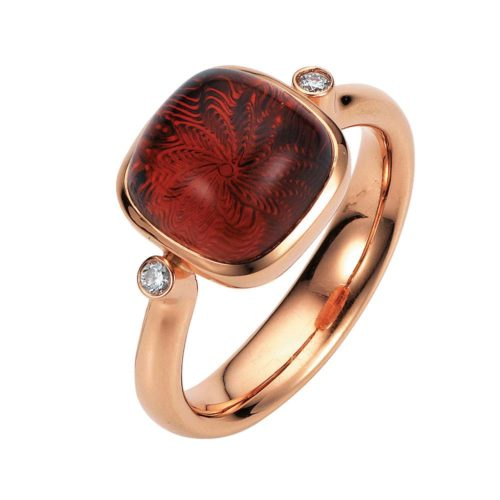Gold ring with red gemstone on guilloched surface with diamonds