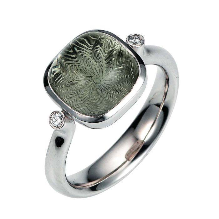 Gold Ring mit grünem Edelstein auf guillochierter Fläche mit Diamanten