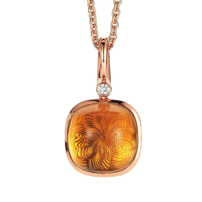 Gold pendant with yellow gemstone on guilloched surface with diamonds