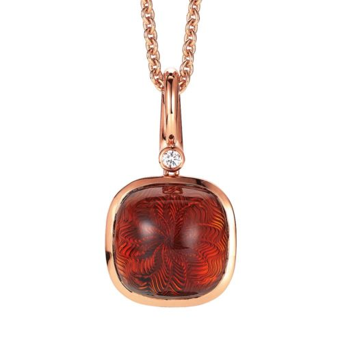 Gold pendant with red gemstone on guilloched surface with diamond