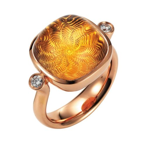 Gold ring with blue gemstone on guilloched surface with diamonds