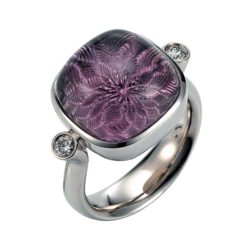 Gold ring with purple gemstone amethyst on guilloched surface with diamonds