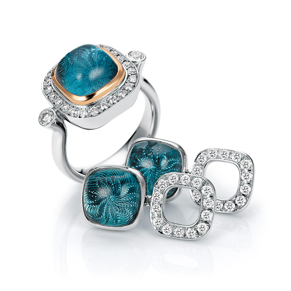 Gold ring with diamonds and blue gemstone on guilloched surface